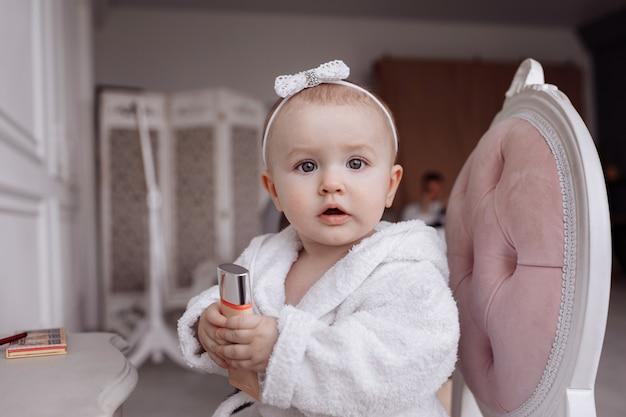 Portret van een schattig klein meisje in een badjas doet make-up en kijkt thuis in de camera.
