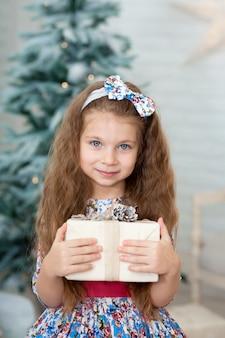 Portret van een schattig klein meisje in een mooie jurk lachend met een doos met een kerstcadeau in haar handen