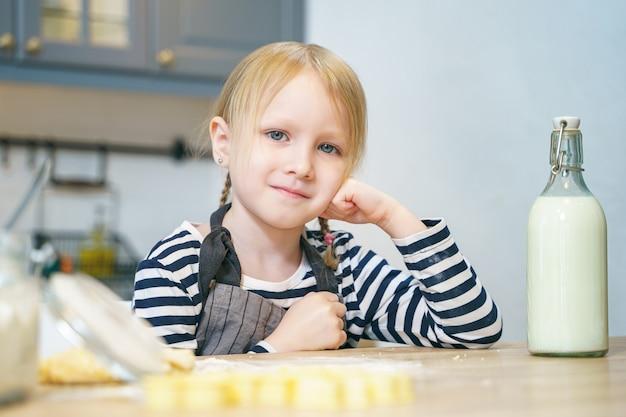 Portret van een schattig klein meisje in een schort deeg voorbereiden op koekjes in de keuken.