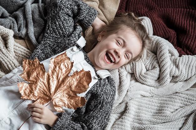 Portret van een schattig klein meisje in een trui met een blad in haar handen.