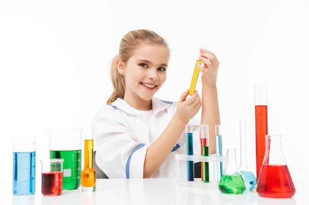 Portret van een schattig klein meisje in een witte laboratoriumjas die chemische experimenten maakt met veelkleurige vloeistof in reageerbuizen geïsoleerd over een witte muur