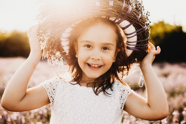 Portret van een schattig klein meisje kijken camera lachen terwijl het houden van een kroon van bloemen op het hoofd tegen zonsondergang op biologisch gebied van bloemen.