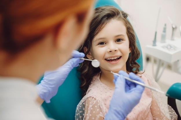 Portret van een schattig klein meisje lachen kijken camera zittend in de stoel stomatologie terwijl pediatrische stomatologist klaar is om tanden onderzoek te doen.