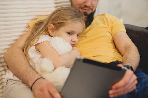 Portret van een schattig klein meisje leunend op de borst van haar vader, een witte teddybeer omhelzen en op zoek naar de tablet van haar vader close-up.