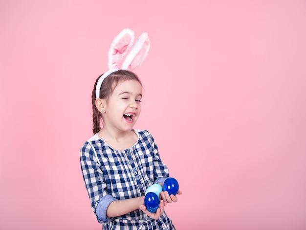 Portret van een schattig klein meisje met paaseieren op een roze achtergrond.
