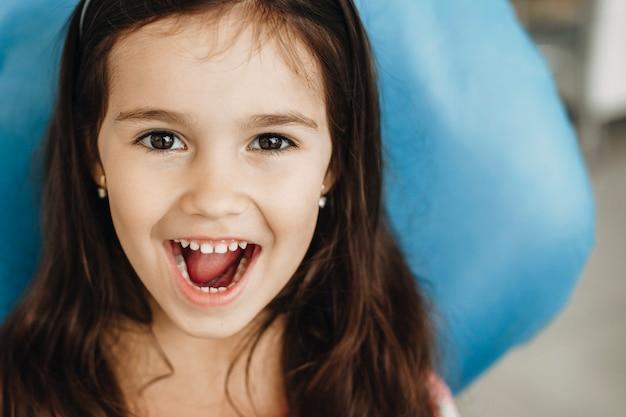 Portret van een schattig klein meisje met tanden na een operatie in een pediatrische kliniek close-up. gelukkig klein kind na tandenonderzoek.