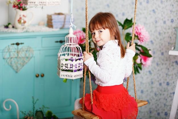 Portret van een schattig klein meisje rijdt op een schommel in het interieur met shabby chic decor