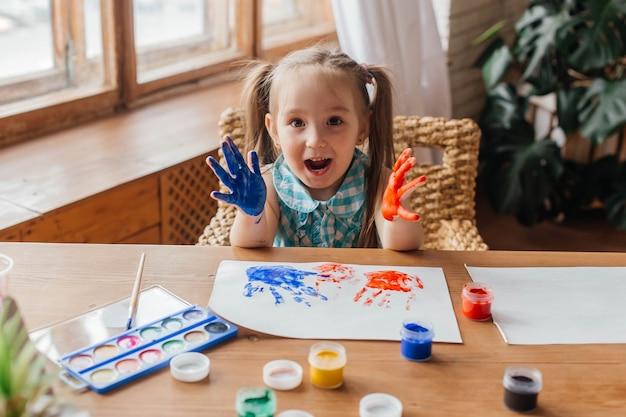 Portret van een schattig klein meisje tekent met verf en handen geschilderde handpalmen voor kinderen