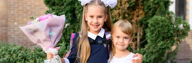 Portret van een schattig klein meisje van zeven jaar oud eersteklasser met een boeket bloemen met haar jongere broer klaar om naar school te gaan. terug naar schoolconcept. banier