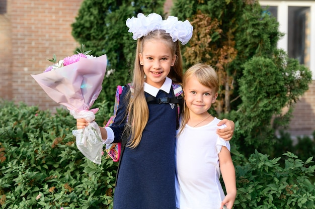 Portret van een schattig klein meisje van zeven jaar oud eersteklasser met een boeket bloemen met haar jongere broer klaar om naar school te gaan. terug naar schoolconcept