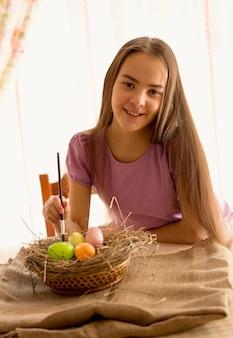 Portret van een schattig lachend meisje dat aan tafel zit met paaseieren