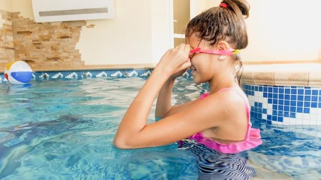 Portret van een schattig lachend meisje dat een zwembril in het zwembad bij het huis zet