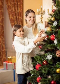 Portret van een schattig lachend meisje dat moeder helpt bij het versieren van de kerstboom