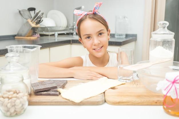 Portret van een schattig lachend meisje dat op een houten kookbord op de keuken leunt