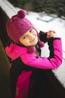 Portret van een schattig lachend meisje dat zich voordeed op straat op een besneeuwde winterdag