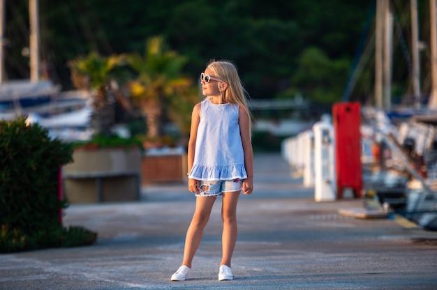 Portret van een schattig lachend meisje met een bril. een meisje in korte broek en een blauwe t-shirt bij zonsondergang aan zee. turkije.