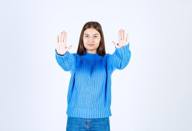 Portret van een schattig meisje dat staat en stopt met zingen op wit.