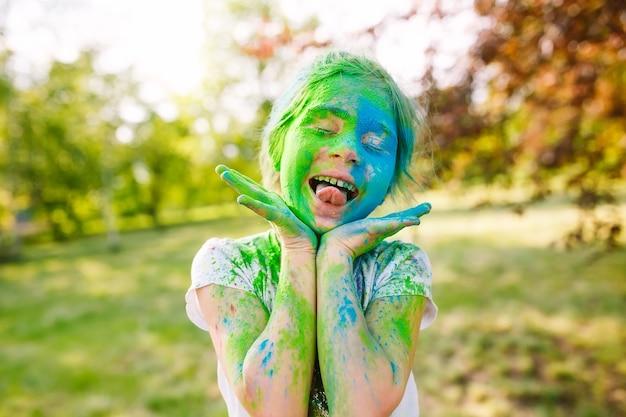 Portret van een schattig meisje geschilderd in de kleuren van het holi-festival