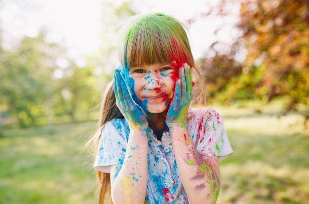 Portret van een schattig meisje geschilderd in de kleuren van het holi-festival.