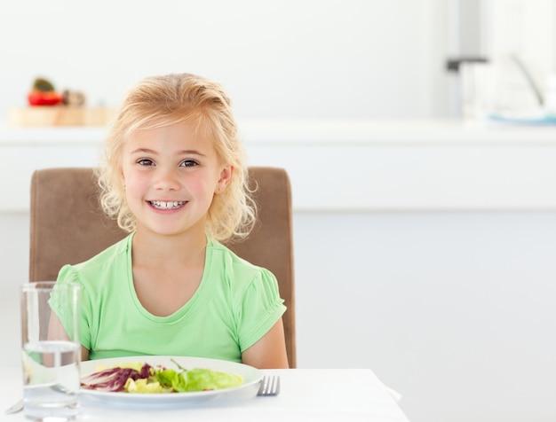 Portret van een schattig meisje het eten van een gezonde salade voor de lunch