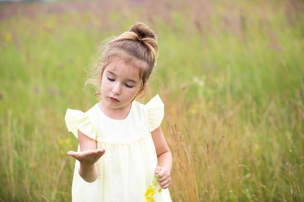 Portret van een schattig meisje in veld met een wilde bloem. jeugd, vakantie op het platteland, vrijheid en zorgeloosheid. zomer tijd. internationale kinderdag. muggenspray, cottage core. ruimte kopiëren