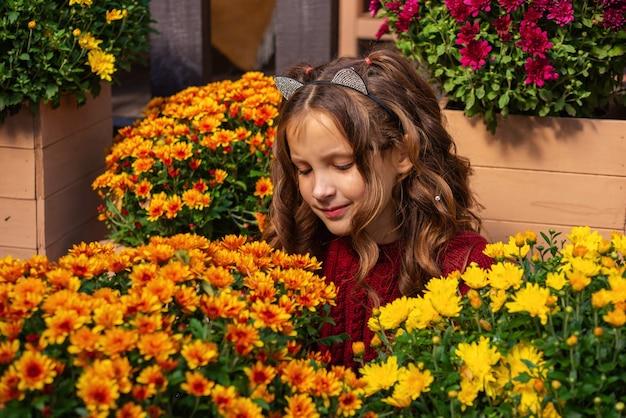 Portret van een schattig meisje met bloemen in de herfst