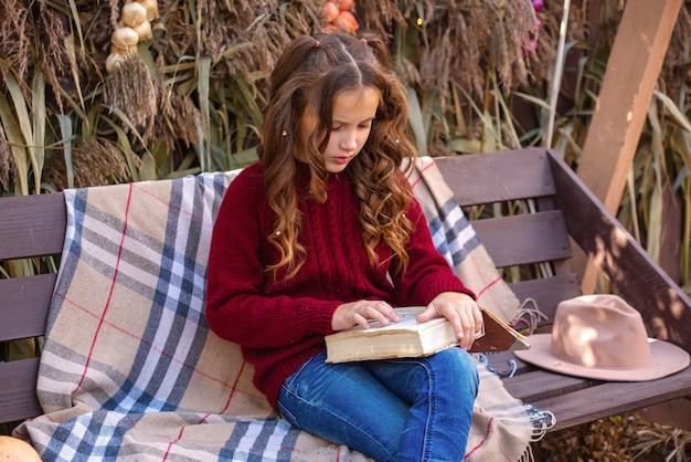 Portret van een schattig meisje met een boek in de herfst op een bankje