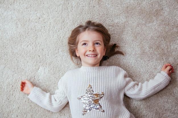 Portret van een schattig meisje op het tapijt