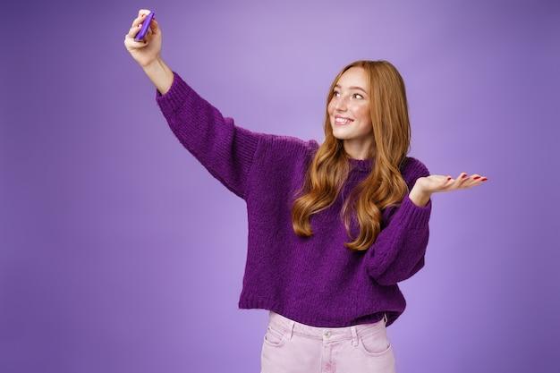 Portret van een schattig roodharig meisje dat op vakantie selfies neemt in de buurt van bezienswaardigheden en de hand opsteekt alsof ze...