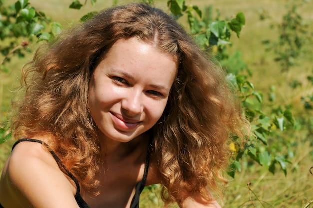 Portret van een schattig roodharig meisje met krullend haar en een natuurlijke huidstructuur met moedervlekken, poriën, puistjes en acne op de natuur buiten in een zonnige zomerdag