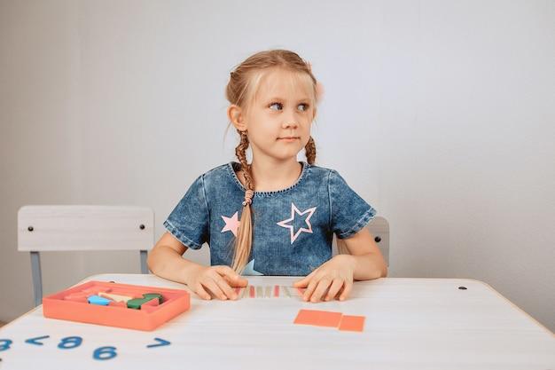 Portret van een schattig schattig kind zittend aan een witte tafel en intellectuele problemen en puzzels op te lossen. kinder ontwikkeling. geest concept. foto met ruis