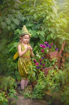 Portret van een schattig schattig meisje in een groene kabouterhoed met een bloem