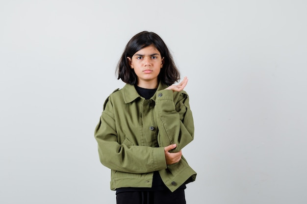 Portret van een schattig tienermeisje dat de palm opzij spreidt terwijl ze mokkend in een legergroen jasje zit en een verbaasd vooraanzicht kijkt