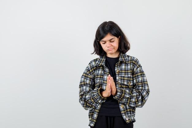 Portret van een schattig tienermeisje dat handen vasthoudt in een biddend gebaar in een geruit hemd en er teleurgesteld uitziet aan de voorkant