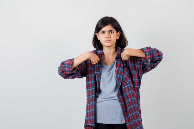 Portret van een schattig tienermeisje dat naar zichzelf wijst in een geruit overhemd en er verward vooraanzicht uitziet