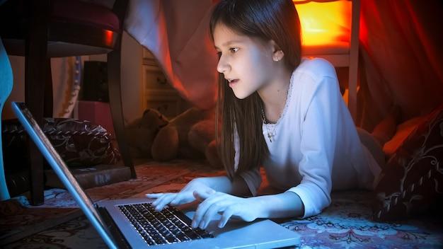 Portret van een schattig tienermeisje dat 's nachts op internet op laptop surft terwijl ze op de vloer in de slaapkamer ligt.