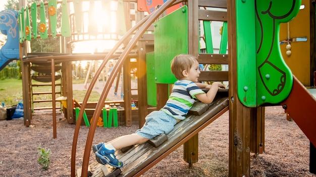 Portret van een schattige 3 jaar oude jongen die op de ladder klimt op de kindergrond in het park