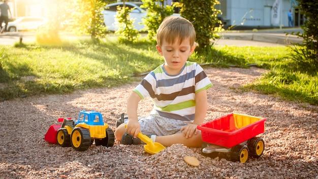 Portret van een schattige 3 jaar oude peuterjongen die op de speelplaats in het park zit en speelt met een kleurrijke plastic speelgoedvrachtwagen