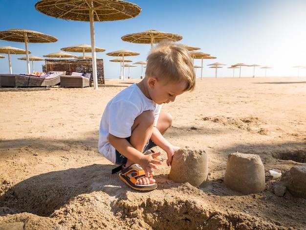 Portret van een schattige 3-jarige peuterjongen die op het zandstrand aan de zee zit en een kasteel bouwt. kind ontspannen op zomervakantie vakantie