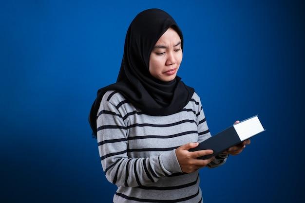 Portret van een schattige aziatische moslimvrouw die ziek en moe is en te veel boeken leest over een blauwe achtergrond