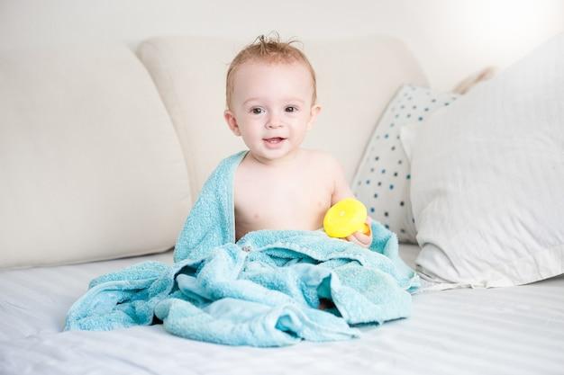 Portret van een schattige baby die op bed zit na een bad?