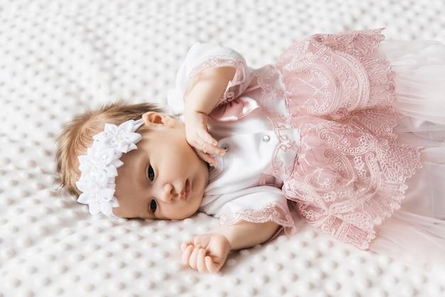 Portret van een schattige baby van 6 maanden oud, een klein meisje in babykleren in een wieg