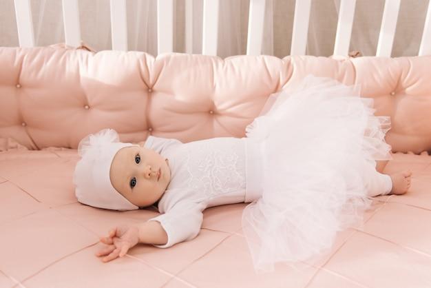 Portret van een schattige baby van 6 maanden oud, een pasgeboren meisje dat in een babybedje ligt
