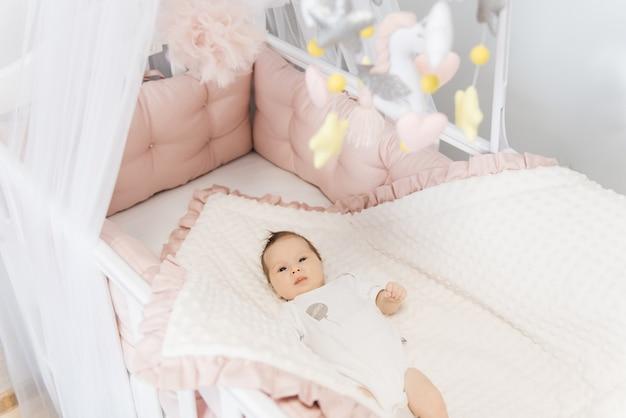 Portret van een schattige baby van 6 maanden oud, een pasgeboren meisje dat in een babywieg ligt
