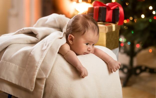 Portret van een schattige babyjongen die in de mand naast de kerstboom ligt