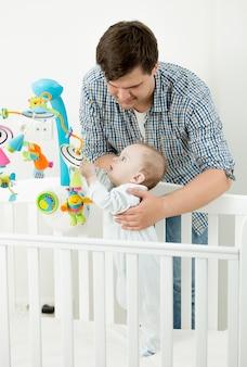 Portret van een schattige babyjongen die met zijn vader in een bedje speelt