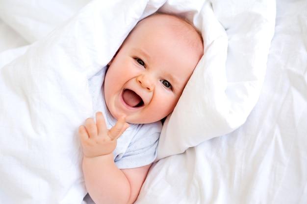 Portret van een schattige babyjongen in katoenwit daarna. textiel voor het kind, hypoallergene materialen.