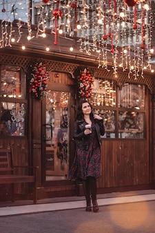 Portret van een schattige brunette vrouw met koffie lopend in de straat versierd met kerstverlichting