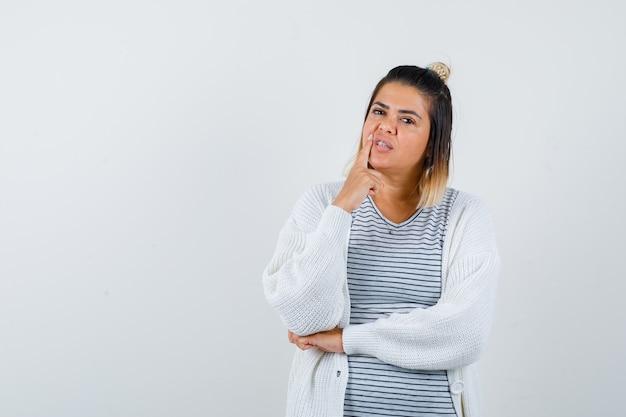 Portret van een schattige dame die de vinger in de buurt van de mond houdt in een t-shirt, vest en er doordacht vooraanzicht uitziet