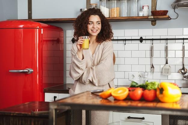 Portret van een schattige europese vrouw die vers sinaasappelsap drinkt tijdens het koken van groentesalade in het keukeninterieur thuis